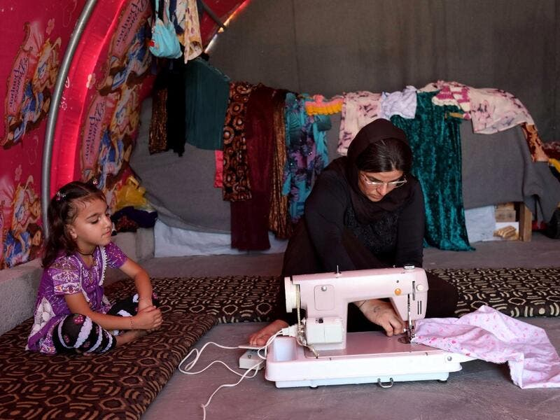 "Iraq's Yazidi survivor Layleh Shemmo sews inside her tent in the Khonke camp for displaced persons in northwestern Iraq on June 24, 2019. Working in the Khonke displacement camp in northwest Iraq, Shemmo glances down at the name tattooed on her left hand: Kero, her husband, still missing five years after the Islamic State group rampaged across the Sinjar region. At the time, IS killed Yazidi men en masse, took boys as child soldiers and sold women as ""sex slaves,"" with survivors streaming into shabby displa"