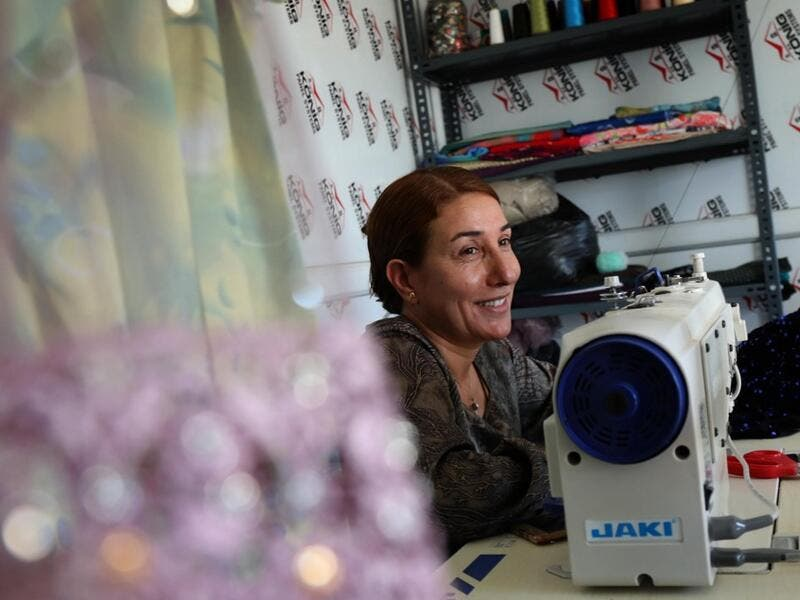 Iraq's Yazidi seamstress Shirin Ghaliyeh, 39, smiles while working at her shop in the Khonke camp for displaced persons in northwestern Iraq on June 24, 2019. SAFIN HAMED / AFP