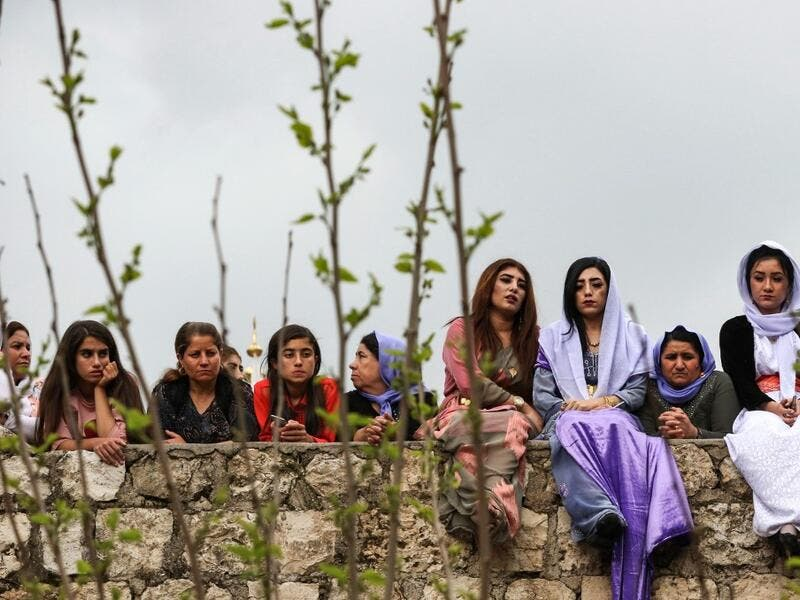 Iraqi Yazidi women sit outside the Temple of Lalish, in a valley near the Kurdish city of Dohuk about 430 kilometres northwest of the capital Baghdad, on April 16, 2019, during a ceremony marking the Yazidi New Year. SAFIN HAMED /