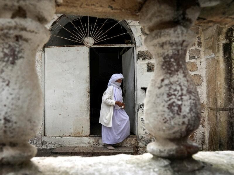 An Iraqi Yazidi visits the Temple of Lalish, in a valley near the Kurdish city of Dohuk about 430 kilometres northwest of the capital Baghdad, on April 16, 2019, during a ceremony marking the Yazidi New Year. Of the 550,000 Yazidis in Iraq before the Islamic State (IS) group invaded their region in 2014, around 100,000 have emigrated abroad and 360,000 remain internally displaced. Roughly 3,300 Yazidis have returned from IS captivity in the last five years, only 10 percent of them men. SAFIN HAMED / AFP