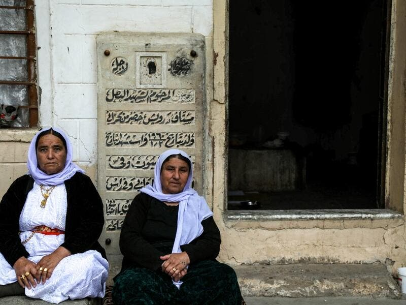 Iraqi Yazidi women sit outside the Temple of Lalish, in a valley near the Kurdish city of Dohuk about 430 kilometres northwest of the capital Baghdad, on April 16, 2019, during a ceremony marking the Yazidi New Year. Roughly 3,300 Yazidis have returned from IS captivity in the last five years, only 10 percent of them men. SAFIN HAMED /