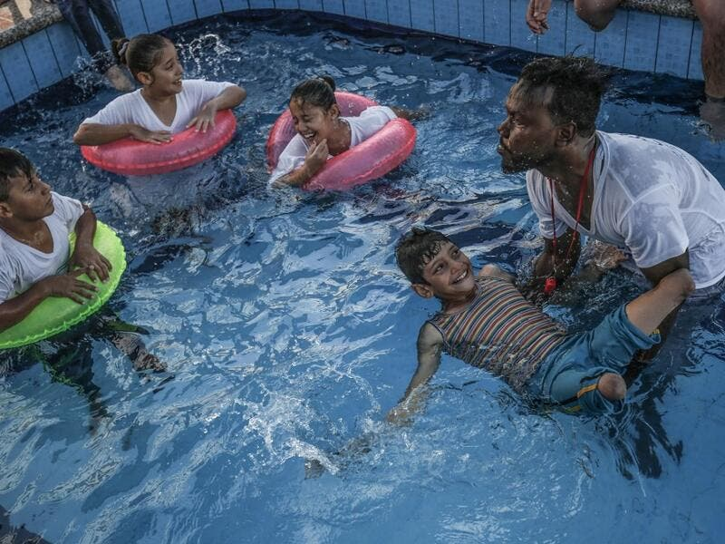 A trainer helps a Palestinian amputee child swim during a summer camp origanized by the Palestinian Children's Relief Fund (PCRF) in the town of Khan Yunis in the southern Gaza strip on August 3, 2019.  SAID KHATIB / AFP