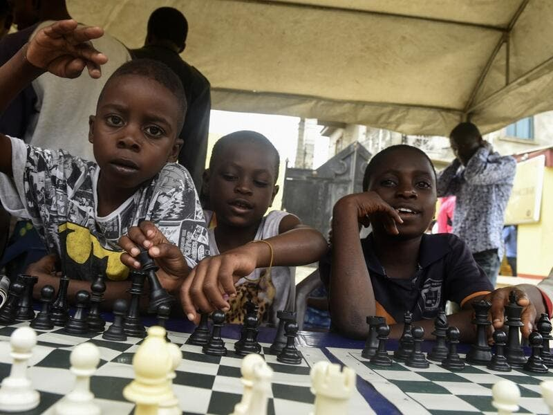 Children sit under a canopy as they play during a chess class at Ogolonto in Ikorodu district of Lagos  PIUS UTOMI EKPEI / AFP