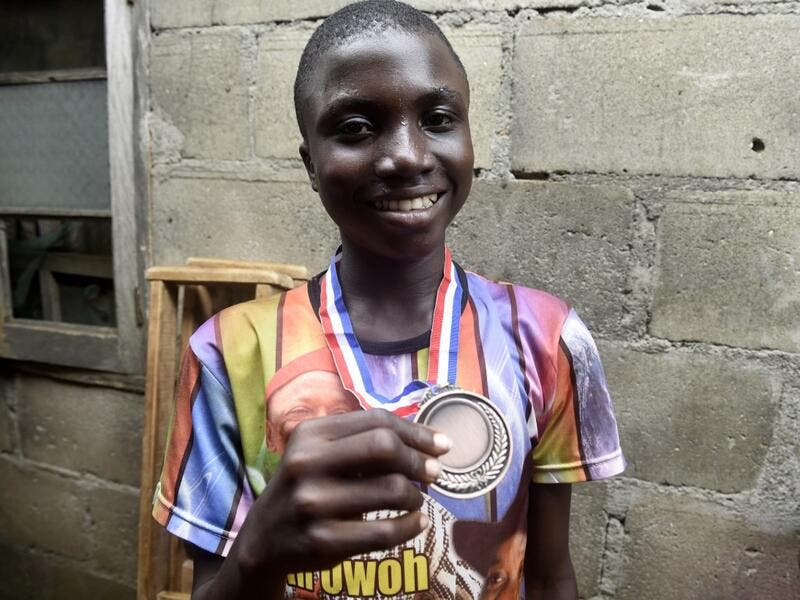 Fourteen-year-old mechanic Jamiu Ninilowo holds a medal he won following a chess tournament at Ogolonto in Ikorodu district of Lagos, on August 17, 2019. In front of chess boards in Lagos, children are busy, concentrating.  PIUS UTOMI EKPEI / AFP