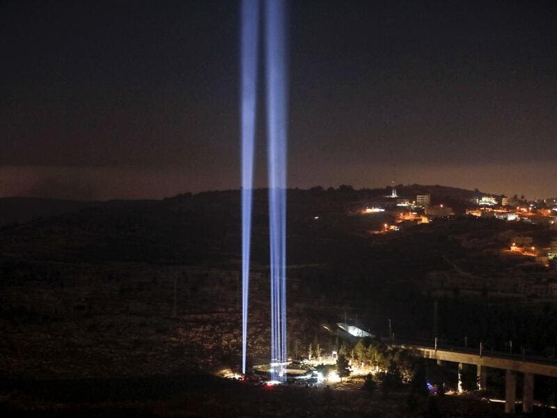 This picture shows a light show in tribute to New York City's World Trade Centre Twin Towers on the eve of the 18th anniversary of the September 11, 2001 terror attacks, at the 9/11 Living Memorial Plaza on a hill overlooking Jerusalem. AHMAD GHARABLI / AFP