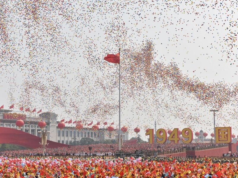 Balloons fly past the national flag at the end of a military parade at Tiananmen Square in Beijing on October 1, 2019, to mark the 70th anniversary of the founding of the People's Republic of China. GREG BAKER / AFP