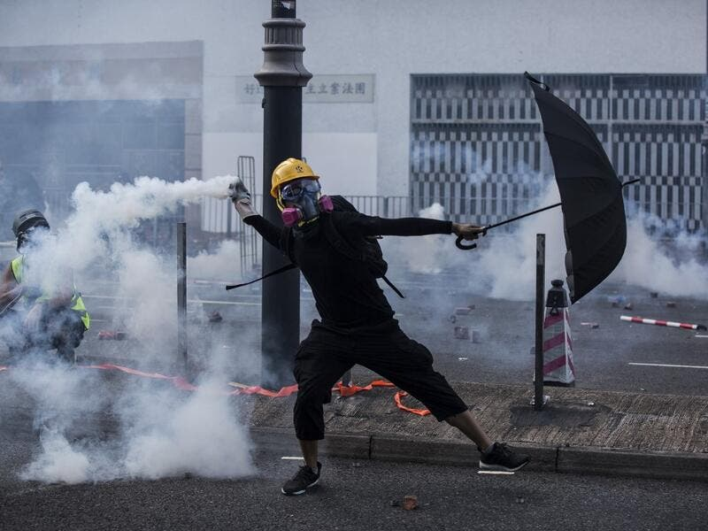 A protester throws a tear gas canister fired by police in the Sha Tin district of Hong Kong on October 1, 2019, as the city observes the National Day holiday to mark the 70th anniversary of communist China's founding. ISAAC LAWRENCE / AFP