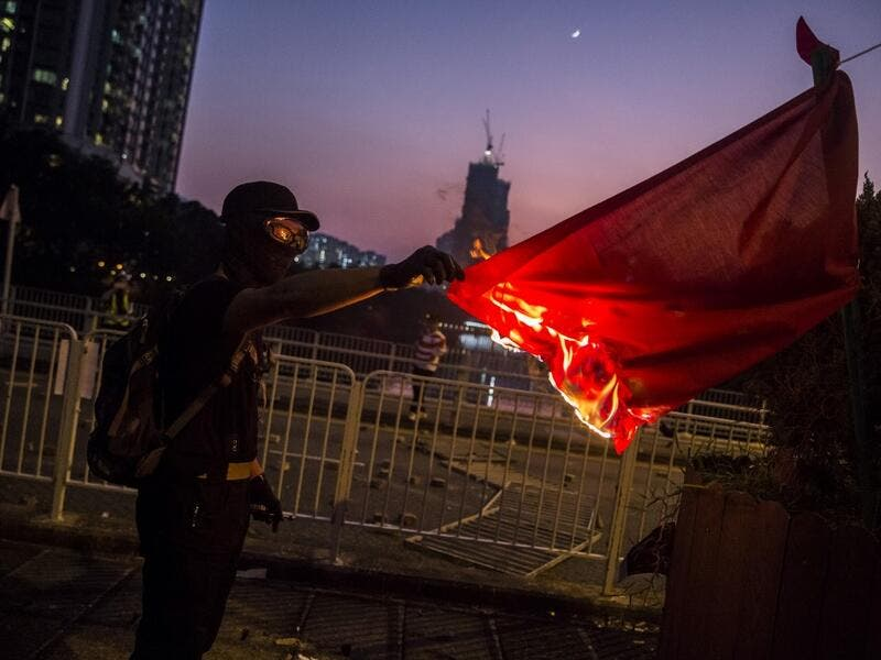 A protester sets fire to the Chinese national flag in the Sha Tin district of Hong Kong on October 1, 2019, as violent demonstrations take place in the streets of the city on the National Day holiday to mark the 70th anniversary of communist China's founding. ISAAC LAWRENCE / AFP