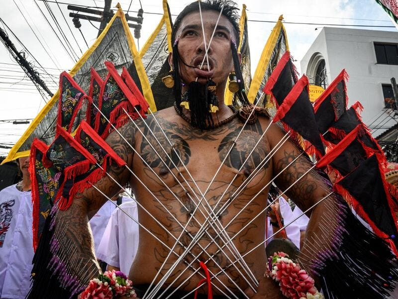A devotee of a Chinese shrine with multiple needles pierced through his cheeks takes part in a procession during the annual Vegetarian Festival in Phuket on October 4, 2019. Mladen ANTONOV / AFP