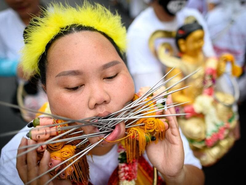 A devotee of a Chinese shrine with multiple skewers pierced through her cheeks takes part in a procession during the annual Vegetarian Festival in Phuket on October 5, 2019. Mladen ANTONOV / AFP