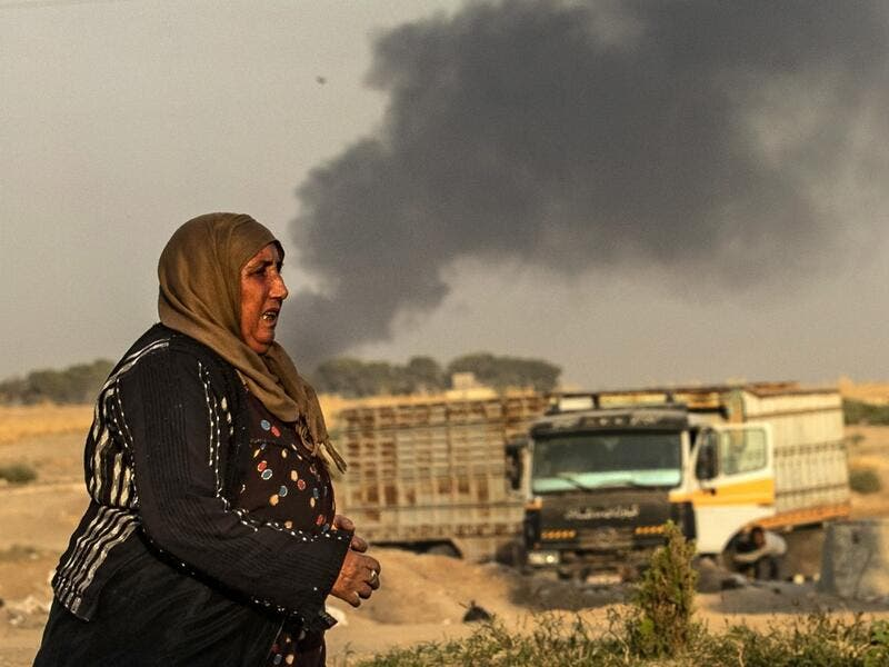 "A woman walks as smoke billows following Turkish bombardment in Syria's northeastern town of Ras al-Ain in the Hasakeh province along the Turkish border on October 9, 2019. Turkey launched an assault on Kurdish forces in northern Syria with air strikes and explosions reported along the border. President Recep Tayyip Erdogan announced the start of the attack on Twitter, labelling it ""Operation Peace Spring"".  Delil SOULEIMAN / AFP"
