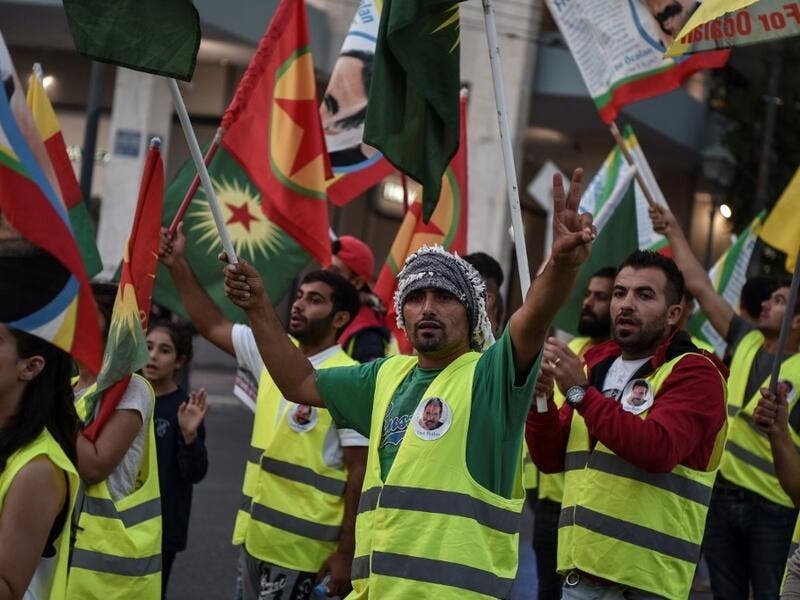 Kurds living in Athens hold flags during a protest near the Turkish embassy in Athens, on October 9, 2019. Louisa GOULIAMAKI / AFP