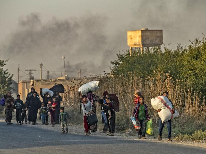 Civilians flee with their belongings amid Turkish bombardment on Syria's northeastern town of Ras al-Ain in the Hasakeh province along the Turkish border on October 9, 2019. Turkey launched a broad assault on Kurdish-controlled areas in northeastern Syria today, with intensive bombardment paving the way for an invasion made possible by the withdrawal of US troops. Delil SOULEIMAN / AFP