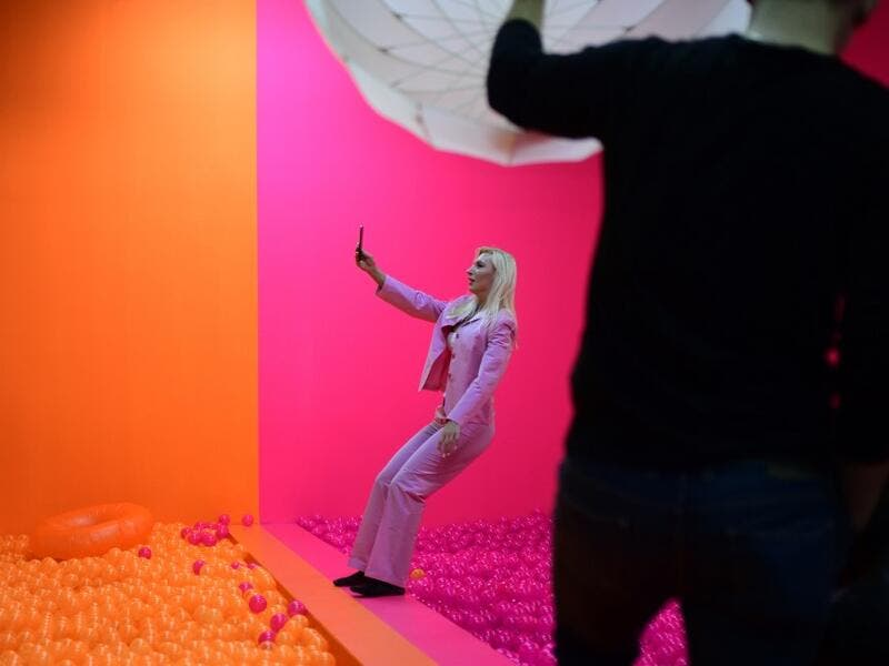 "A woman photographs herself as she falls into a ball bath at the ""Supercandy Pop-Up Museum Vol. 2"" in Cologne, western Germany on November 1, 2019. It is an interactive museum and offers a photo backdrop for social media at 25 stations. INA FASSBENDER / AFP"