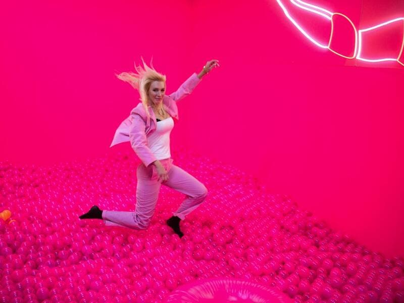 "A woman jumps into a ball bath at the ""Supercandy Pop-Up Museum Vol. 2"" in Cologne, western Germany on November 1, 2019. It is an interactive museum and offers a photo backdrop for social media at 25 stations. INA FASSBENDER / AFP"