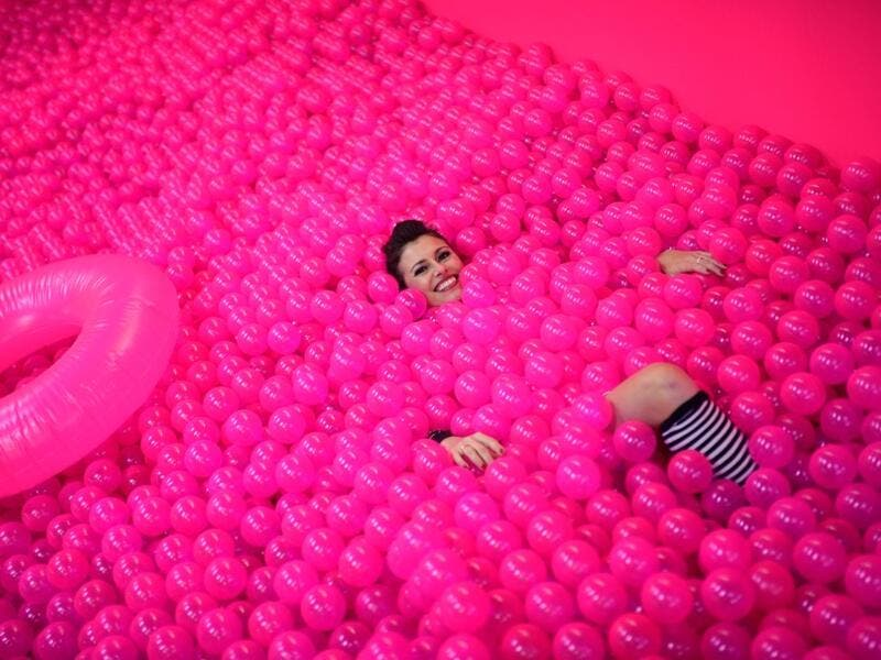 "A woman smiles, while lying in a ball bath, at the ""Supercandy Pop-Up Museum Vol. 2"" in Cologne, western Germany on November 1, 2019. It is an interactive museum and offers a photo backdrop for social media at 25 stations. INA FASSBENDER / AFP"