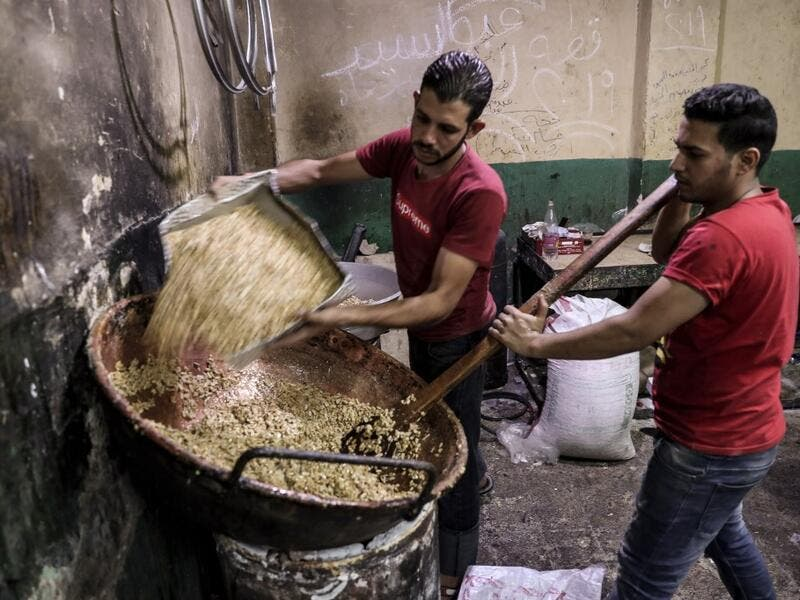 "Egyptian confectioners add peanuts to melted sugar as they make sweets at a candy factory in the capital Cairo on November 2, 2019, ahead of celebrations of the Muslim Prophet Mohammed's birthday, known as ""Al Mawlid Al Nabawi"". Prophet Mohamed was born in Saudi Arabia's arid mountainous city of Mecca, the holiest in Islam, some 1490 years ago. Sunni Muslims in many parts of the world celebrate his birthday on the 12th day of the third month of the Islamic calendar, which will fall this year on November 9th"