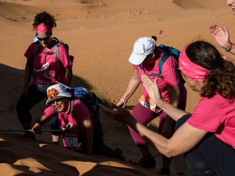 "Women encourage each other as they take part in the desert trek ""Rose Trip Maroc"", on November 4, 2019 in the erg Chebbi near Merzouga. The Rose Trip Maroc is a female-oriented trek where teams of three must travel through the southern Moroccan Sahara desert with a compass, a map and a topographical reporter. JEAN-PHILIPPE KSIAZEK / AFP"