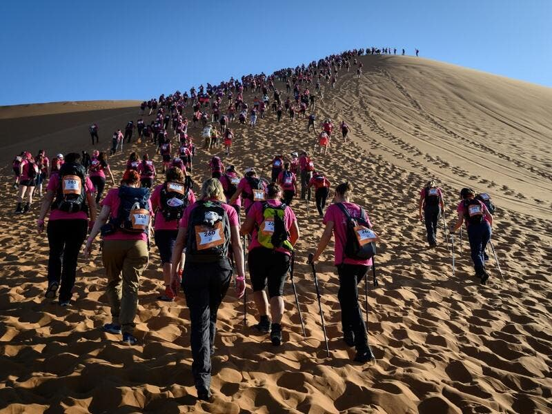 "Women climb up a sand dune as they take part in the desert trek ""Rose Trip Maroc"", on November 4, 2019 in the erg Chebbi near Merzouga. The Rose Trip Maroc is a female-oriented trek where teams of three must travel through the southern Moroccan Sahara desert with a compass, a map and a topographical reporter. JEAN-PHILIPPE KSIAZEK / AFP"