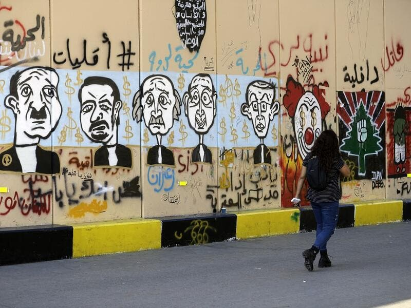 A woman walks past graffitis sprayed on a wall in Lebanon's capital Beirut on November 6, 2019. Since October 17, the chanting of tens of thousands of Lebanese denouncing the political elite have shaken the normally staid district around two Beirut squares, Martyrs' and Riad Al Solh. JOSEPH EID / AFP
