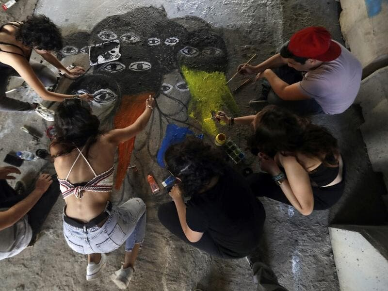 Lebanese anti-government protesters paint a graffiti on the ground in central Beirut on November 5, 2019. Since October 17, the chanting of tens of thousands of Lebanese denouncing the political elite have shaken the normally staid district around two Beirut squares, Martyrs' and Riad Al Solh. JOSEPH EID / AFP