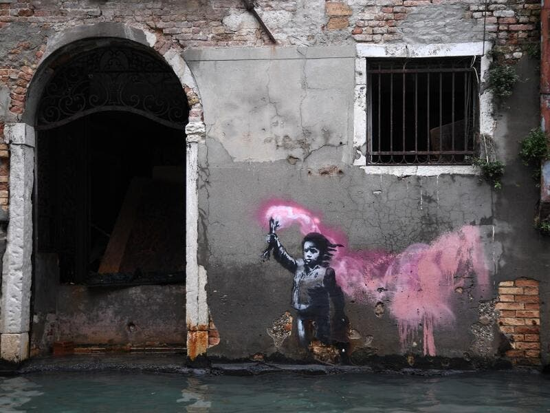 "The artwork by street artist Banksy, that portrays a migrant child wearing a lifejacket and holding a neon pink flare, is pictured after an exceptional overnight ""Alta Acqua"" high tide water level, on November 13, 2019 in Venice. Venice was hit by the highest tide in more than 50 years late November 12, with tourists wading through flooded streets to seek shelter as a fierce wind whipped up waves in St. Mark's Square. Marco Bertorello / AFP"