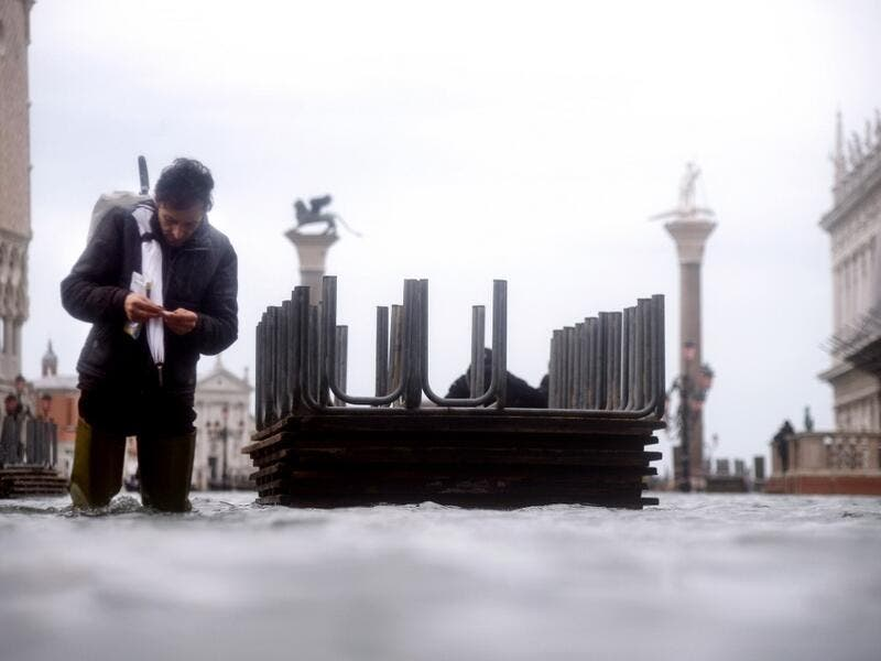 A man prepares a cigarette as he walks in the water of the flooded St. Mark's Square, on November 15, 2019 in Venice, two days after the city suffered its highest tide in 50 years. Flood-hit Venice was bracing for another exceptional high tide on November 15, as Italy declared a state of emergency for the UNESCO city where perilous deluges have caused millions of euros worth of damage. Filippo MONTEFORTE / AFP