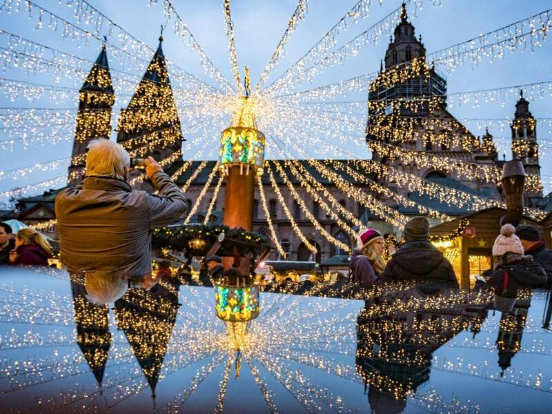 A man photographs the cathedral and the festive lighting of the Christmas market as they mirror on a polished surface in Mainz, Germany, on December 6, 2019.  Frank Rumpenhorst / dpa / AFP