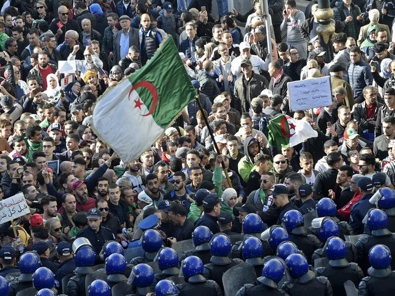 Algerian security surround protesters during an anti-government demonstration in the capital Algiers on December 11, 2019, ahead of the presidential vote scheduled for December 12. Algeria's contentious presidential election campaign is highlighting the vast gap between youth at the heart of a reformist protest movement and an ageing elite they see as clinging to power. RYAD KRAMDI / AFP