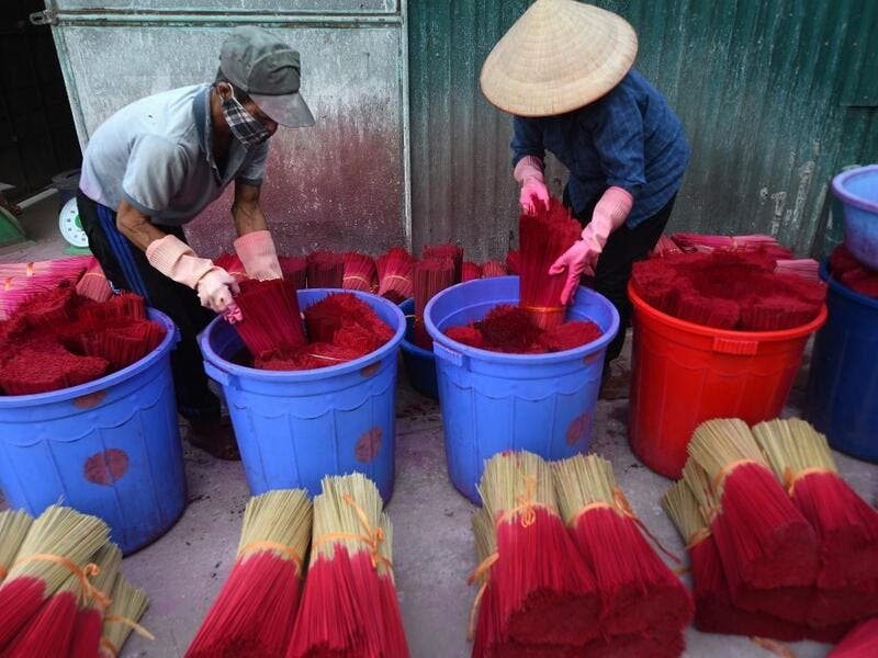 Vietnamese workers dye incense sticks in Quang Phu Cau village on the outskirts of Hanoi on January 9, 2020 ahead of the upcoming Lunar New Year celebrations, referred to in Vietnam as Tet. Nhac NGUYEN / AFP