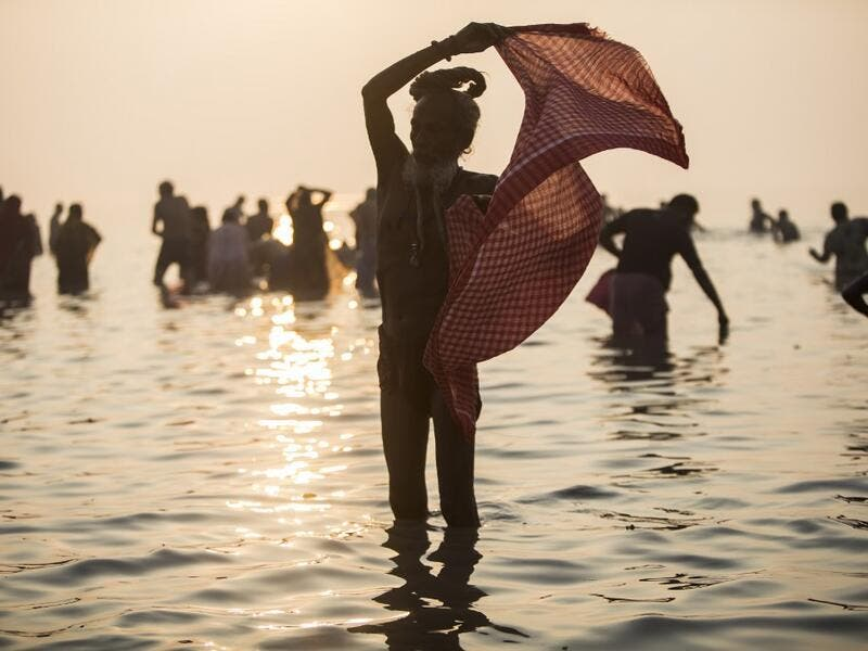A Hindu Sadhu (holy man) takes a holy dip in the Bay of Bengal during the Gangasagar Mela, at Sagar Island, some 150 kilometres south of Kolkata on January 14, 2020. XAVIER GALIANA / AFP