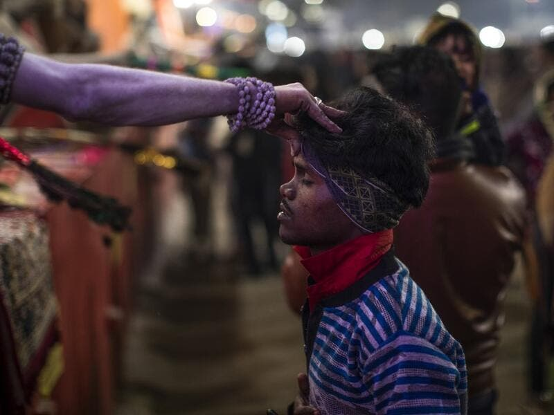 A Sadhu (Hindu holy man) blesses a pilgrim during the Gangasagar Mela, at Sagar Island, some 150 kilometres south of Kolkata on January 14, 2020. XAVIER GALIANA / AFP
