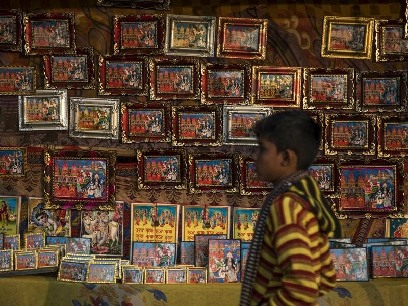 A young Hindu devotee walks past a stall selling religious images during the Gangasagar Mela, at Sagar Island, some 150 kilometres south of Kolkata on January 14, 2020. XAVIER GALIANA / AFP