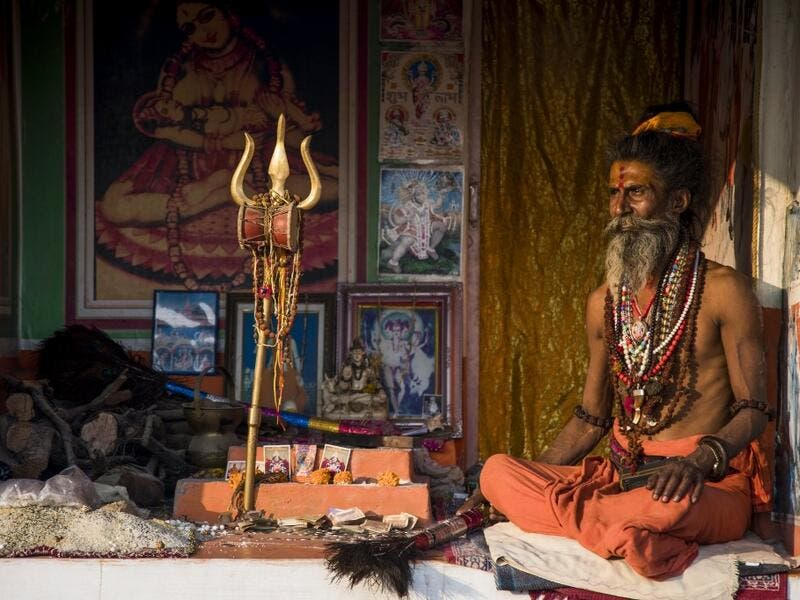 A Hindu Sadhu (holy man) waits to offer blessings to devotees at a temporary camp during the Gangasagar Mela, at Sagar Island, around 150 kilometres south of Kolkata on January 14, 2020. Xavier GALIANA / AFP