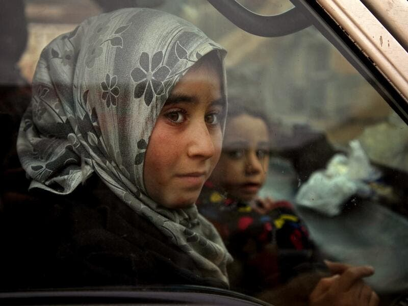 Displaced Syrian girls look on from within a vehicle passing through the town of Hazano in the northern countryside of Idlib, on February 4, 2020, fleeing northwards amid an ongoing regime offensive. A Russian-backed Syrian government offensive against the country's last rebel enclave of Idlib has displaced more than half a million people in two months, according to the United Nations. The wave of displacement, which coincides with a biting winter, is one of the largest since the start of the Syrian war nea