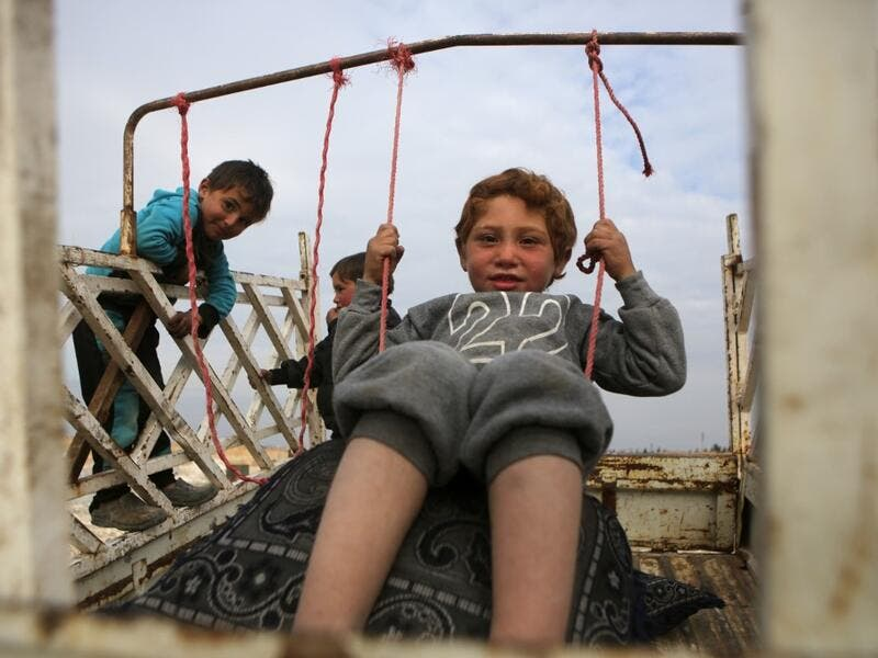 A child sits in a make-shift swing in the back of a truck in the vicinity of the northern Syrian town of Tal Abyad on February 4, 2020, where many families from the south of Aleppo province have fled to following Syrian government forces' bombardment. Bakr ALKASEM / AFP