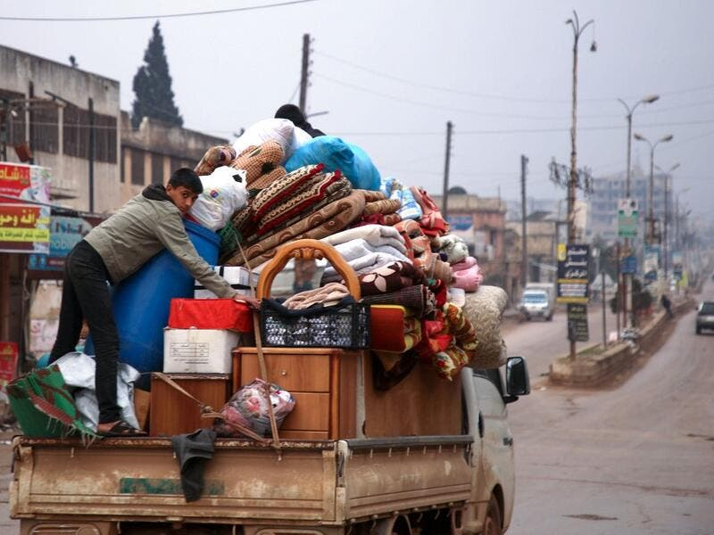 A Syrian youth climbs atop belongings in the back of a truck as people leave the town of Binnish in the northwestern province of Idlib, on February 4, 2020, amid an ongoing offensive by pro-regime forces. A Russian-backed Syrian government offensive against the country's last rebel enclave of Idlib has displaced more than half a million people in two months, according to the United Nations. The wave of displacement, which coincides with a biting winter, is one of the largest since the start of the Syrian wa