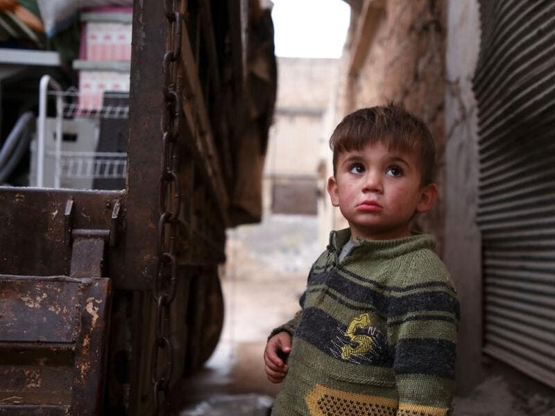 A Syrian child looks up as relatives load belongings onto a truck ahead of leaving the town of Binnish in the northwestern province of Idlib, on February 4, 2020, amid an ongoing offensive by pro-regime forces. A Russian-backed Syrian government offensive against the country's last rebel enclave of Idlib has displaced more than half a million people in two months, according to the United Nations. The wave of displacement, which coincides with a biting winter, is one of the largest since the start of the Syr