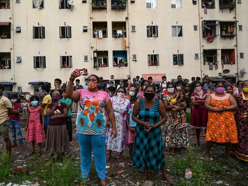 Residents watch a music band formed by Sri Lankan Navy personnel as they play outside a housing complex during a government-imposed nationwide lockdown as a preventive measure against the COVID-19 coronavirus, in Colombo on April 9, 2020. ISHARA S. KODIKARA / AFP