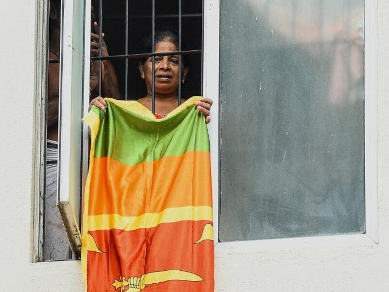 Residents watch from their flat's window a music band formed by Sri Lankan Navy personnel as they play outside a housing complex during a government-imposed nationwide lockdown as a preventive measure against the COVID-19 coronavirus, in Colombo on April 9, 2020. ISHARA S. KODIKARA / AFP