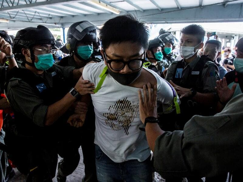 Police officers arrest a pro-democracy demonstrator (C) during a pro-democracy protest calling for the city's independence in Hong Kong on May 10, 2020. ISAAC LAWRENCE / AFP