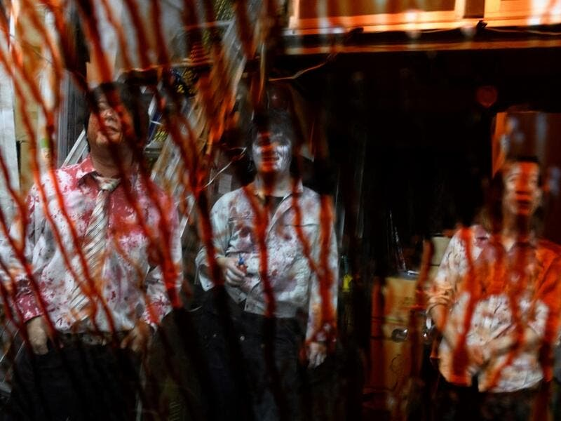 This picture taken on June 15, 2020 shows fake blood on the window of a car as actors (L-R) Kota Hanegawa, 28, Kenta Iwana, 25, and Asami Takeuchi, 33, rest after a demonstration of a drive-in haunted house at a garage in Tokyo. Philip FONG / AFP