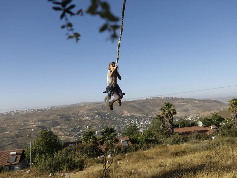 A girl swings at a park in the Israeli Yitzhar settlement south of the Palestinian city of Nablus in the occupied the West Bank on June 22, 2020. The government of Israeli Prime Minister Benjamin Netanyahu has said it could begin the process to annex Jewish settlements in the West Bank as well as the strategic Jordan Valley from July 1.The plan -- endorsed by Washington -- would see the creation of a Palestinian state, but on reduced territory, and without Palestinians' core demand of a capital in east Jeru