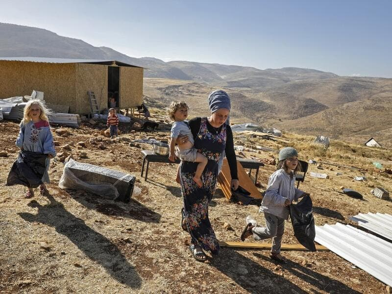 An Israeli settler woman walks with children in the Maoz Ester outpost located next to the Israeli settlement of Kokhav HaShahar in the occupied West Bank on June 18, 2020. The government of Israeli Prime Minister Benjamin Netanyahu has said it could begin the process to annex Jewish settlements in the West Bank as well as the strategic Jordan Valley from July 1. The plan -- endorsed by Washington -- would see the creation of a Palestinian state, but on reduced territory, and without Palestinians' core dema