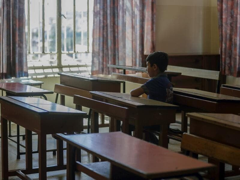 A Lebanese pupil looks out of the window as he sits in his empty classroom after coming to collect the books he left before the COVID-19 lockdown, at Our Lady of Lourdes school in the Lebanese city of Zahle, in the central Bekaa region, on June 30, 2020. (AFP)