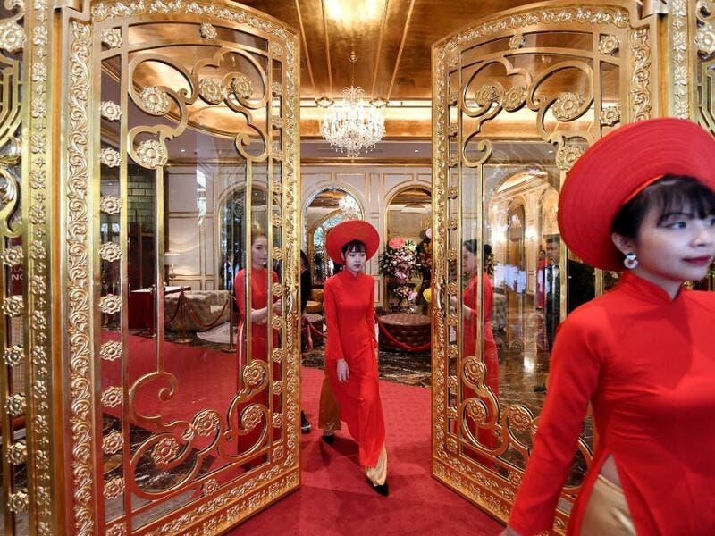 Staff wait to welcome guests in the lobby of the newly-inaugurated Dolce Hanoi Golden Lake hotel, the world's first gold-plated hotel, in Hanoi on July 2, 2020. Manan VATSYAYANA / AFP