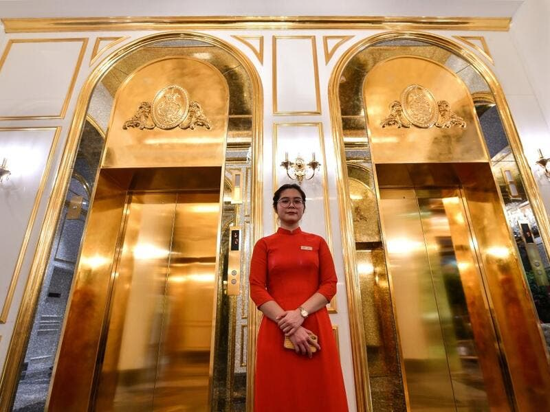 A staff member stands near the lifts in the lobby of the newly-inaugurated Dolce Hanoi Golden Lake hotel, the world's first gold-plated hotel, in Hanoi on July 2, 2020. Manan VATSYAYANA / AFP