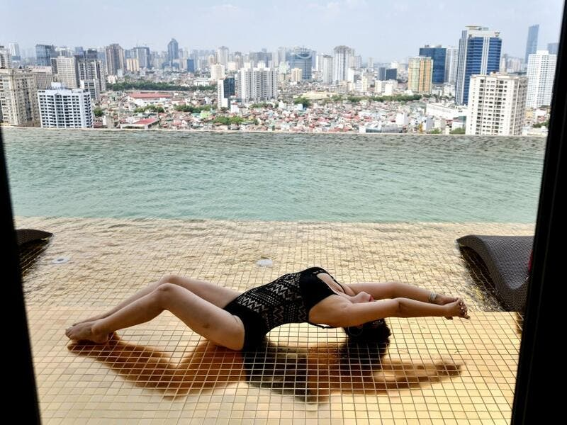 A guest poses for photographs at the infinity pool of the newly-inaugurated Dolce Hanoi Golden Lake hotel, the world's first gold-plated hotel, in Hanoi on July 2, 2020. Manan VATSYAYANA / AFP