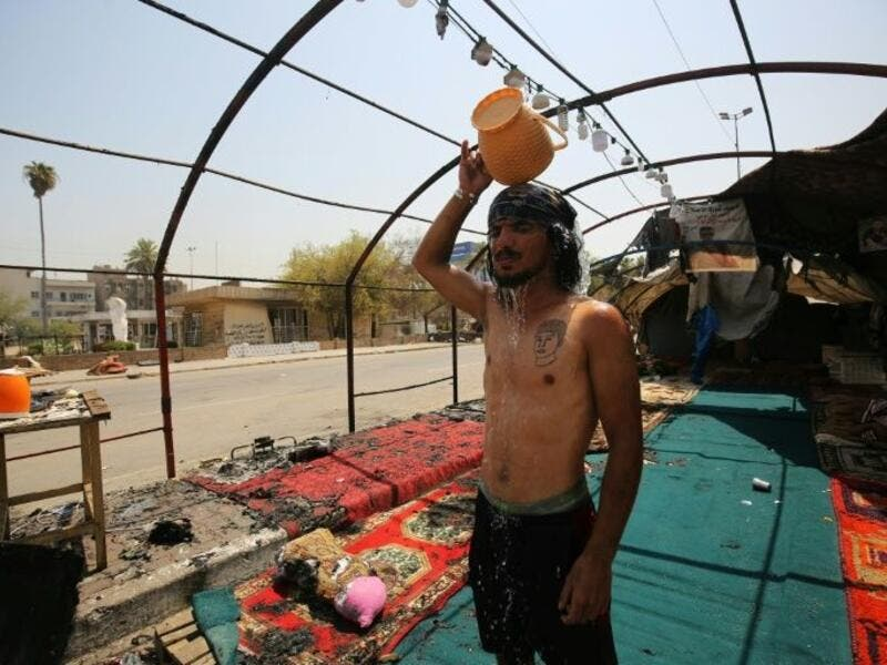 An Iraqi youth pours water over his head to cool down as temperatures soared in Baghdad, standing amid the remains of a protest tent that was burnt the previous night in the capital's Tahrir Square (AFP Photo/AHMAD AL-RUBAYE)