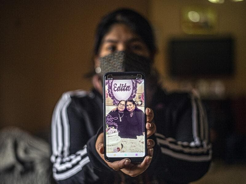 Peruvian Julizza Navarro, 32, shows a picture of her mother Maribel Diaz (R), 52, and her grandmother Edita Leiva (L), 76, who died from COVID-19, at her home in Chorrillos, south of Lima, Peru on August 11, 2020. Global deaths from the coronavirus have almost reached on September 25, 2020 the grim threshold of one million. Around one-third of fatalities were in Latin America, where countries with overstretched medical resources are preparing for a further onslaught. ERNESTO BENAVIDES / AFP